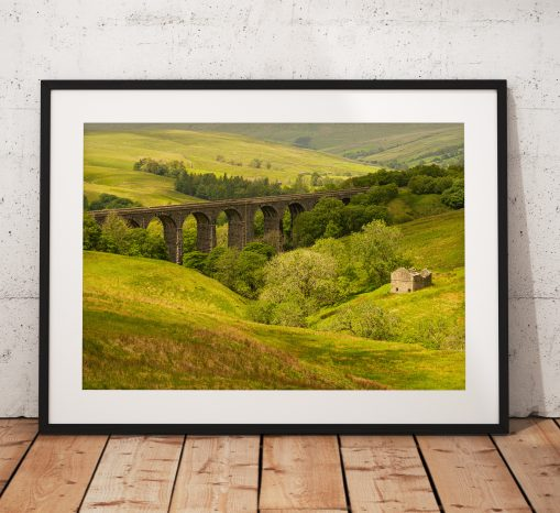 Photo of Dent Viaduct and ruined barn surrounded by lush woodland in the Yorkshire Dales. England